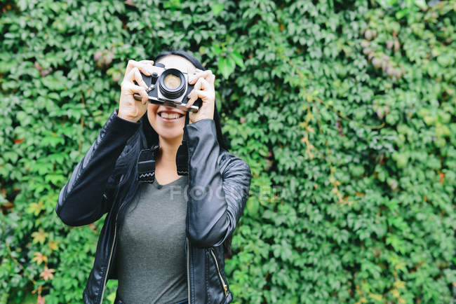 Young woman taking pictures with analogue camera — Stock Photo