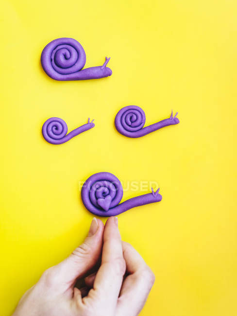 Hand putting heart on snail family made from modelling clay — Stock Photo