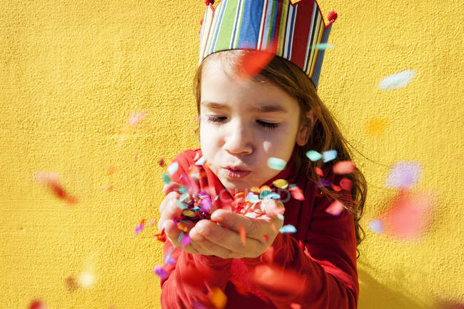Portrait of little girl wearing paper crown blowing confetti — Stock Photo