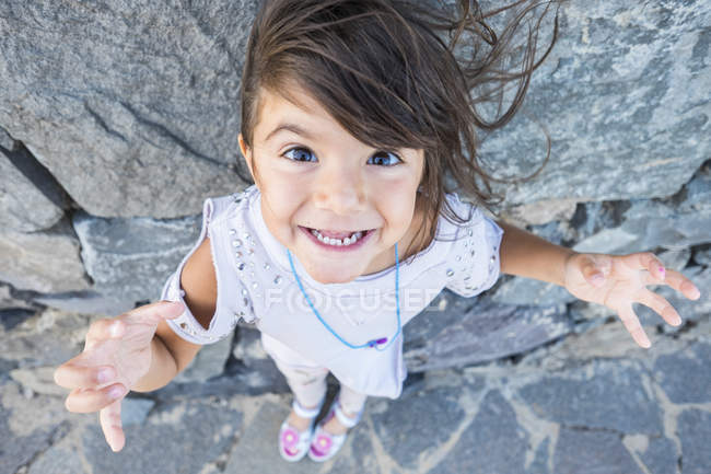 Portrait of staring little girl with blowing hair in front of a rock face — Stock Photo