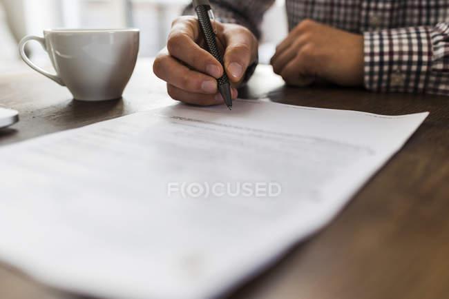 Cortada a imagem do homem que assinar o documento na mesa — Fotografia de Stock