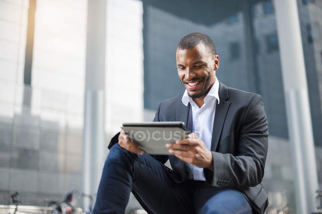 Усміхаючись бізнесмен використання планшетного перед Офісна будівля — стокове фото