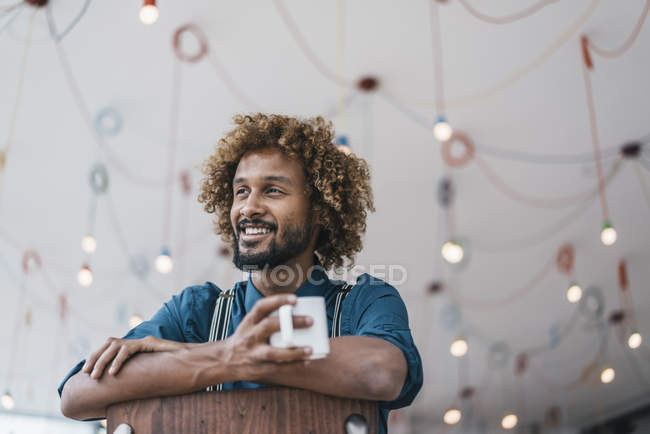 Young man sitting on chair and holding coffee in office — Stock Photo