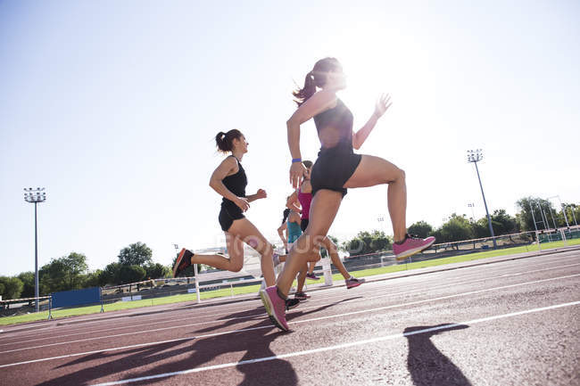 Female runners on tartan track, side view — Stock Photo