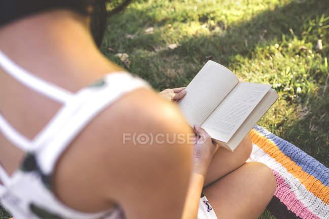 Крупный план женщины, сидящей на одеяле, читающей книгу — стоковое фото