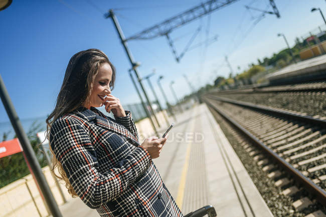 Smiling woman on platform looking at cell phone — Stock Photo