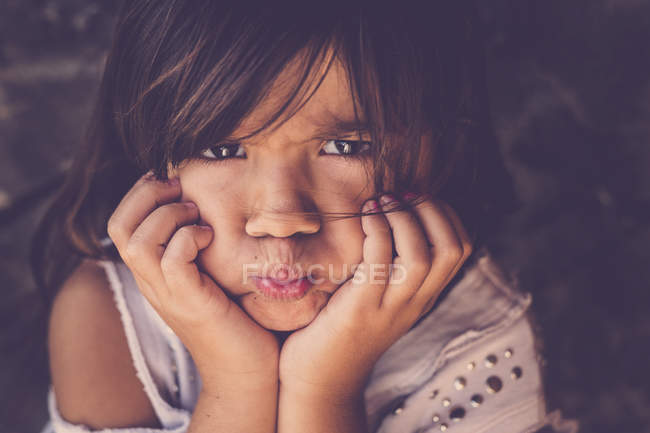 Portrait of girl pouting mouth with head in her hands — Stock Photo