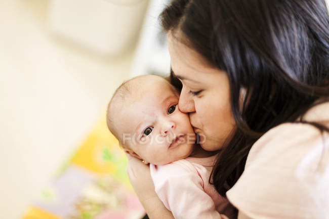 Mature mother kissing her baby girl at home — Stock Photo