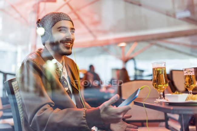 Homem sorridente com fones de ouvido e o telefone celular no bar ao ar livre — Fotografia de Stock
