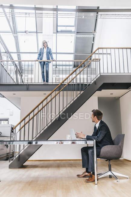 Бізнесмен, сидячи на столі в офісі з бізнес-леді на верхньому поверсі — стокове фото