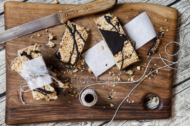 Hausgemachte Müsliriegel mit Amaranth und dunkler Schokolade auf Holzbrett — Stockfoto