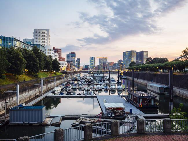 Alemania, Dusseldorf, ve al puerto de los medios de comunicación con el puerto de la ciudad en primer plano - foto de stock