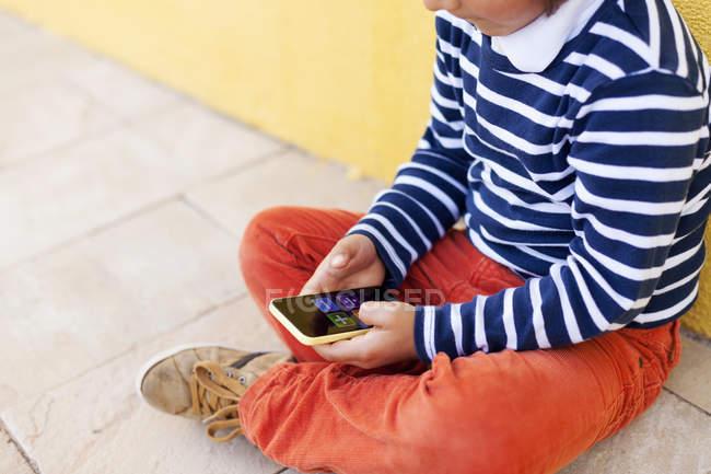 Bambino seduto sul marciapiede a giocare con lo smartphone — Foto stock