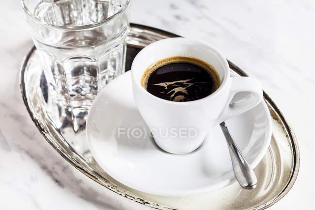 Vista del primo piano dell'espresso e del bicchiere d'acqua sul vassoio di metallo — Foto stock
