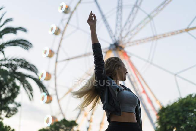 Jeune enthousiaste sur la fête foraine avec une grande roue — Photo de stock