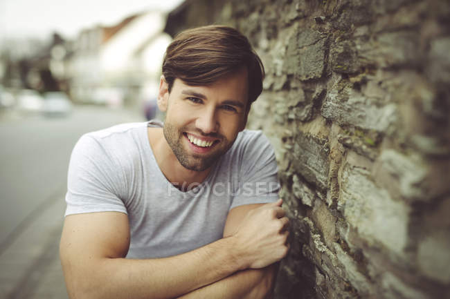 Smiling man wearing t-shirt leaning against stone wall — Stock Photo