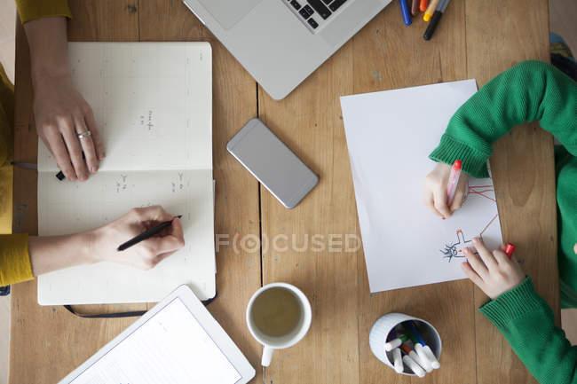 Immagine ritagliata della donna che scrive nel taccuino con il disegno del figlio alla tavola — Foto stock
