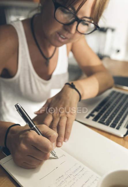 Жінка з ноутбука в бюро, писати в книзі — стокове фото