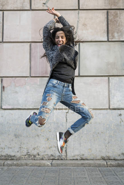 Portrait of exuberant young woman jumping around — Stock Photo