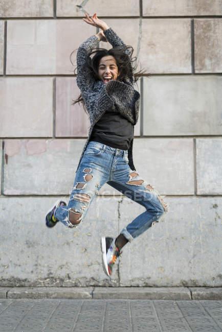 Портрет exuberant молода жінка стрибав — стокове фото