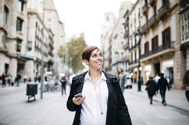 Pregnant woman with cell phone walking in the city — Stock Photo