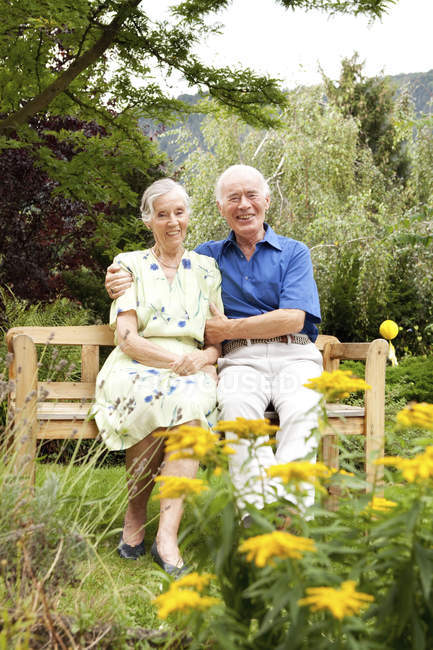 Confident senior couple sitting on bench in garden — Stock Photo