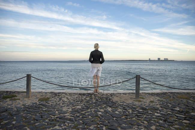 Portugal, Setúbal, Mujer de pie en el mar mirando a Troia penninsula - foto de stock