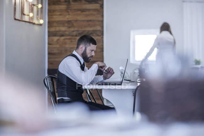 Gestionnaire de restaurant travaillant à l'ordinateur portable — Photo de stock