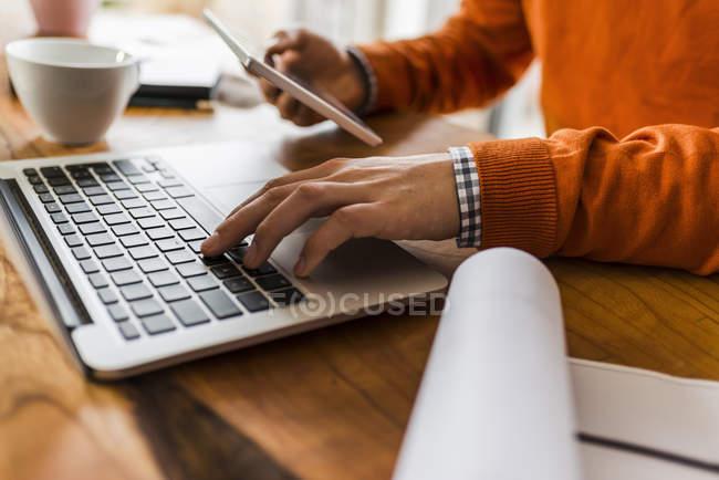 Immagine ritagliata dell'uomo utilizzando phablet e laptop alla scrivania — Foto stock