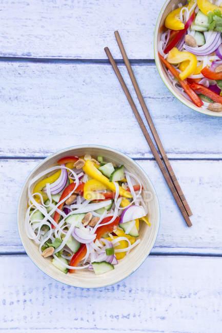 Чаши из стекла лапши Салат с овощами на белое дерево — стоковое фото