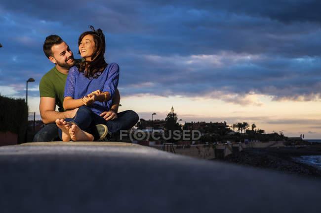 Glückliches junges Paar sitzt am Meer — Stockfoto