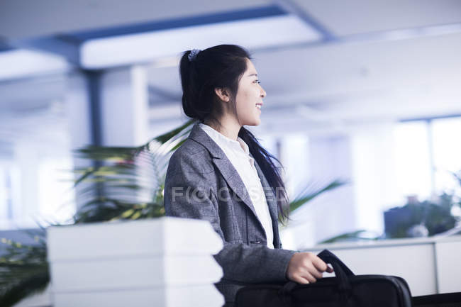 Young Chinese woman with briefcase in office — Stock Photo