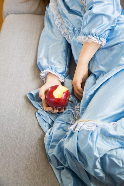 Little girl dressed up as princess holding bitten red apple — Stock Photo