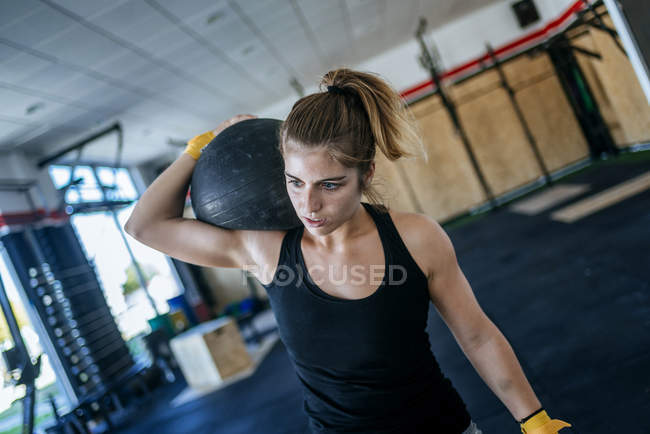 Caucasian sporty woman exercising with ball in gym — Stock Photo