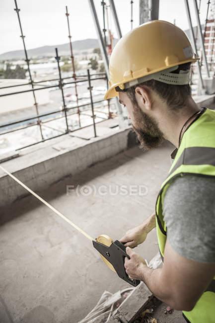 Trabalhador da construção civil usando a fita métrica no canteiro de obras — Fotografia de Stock