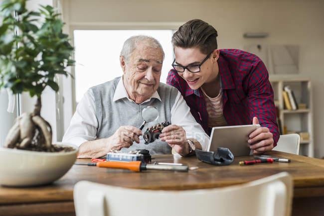 Senior hombre y nieto con juguete tren y mini tablet en casa - foto de stock
