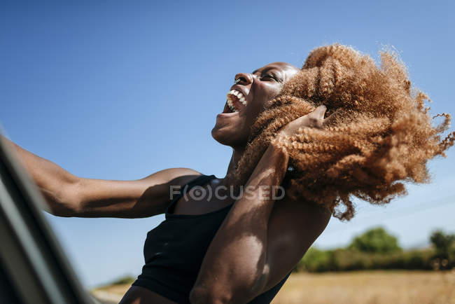 Excited young woman leaning out of car window — Stock Photo
