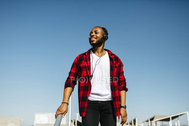 Smiling man listening to music with headphones outdoor — Stock Photo