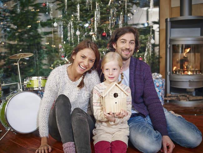 Eltern sitzen mit Tochter vor dem Weihnachtsbaum und lächeln — Stockfoto