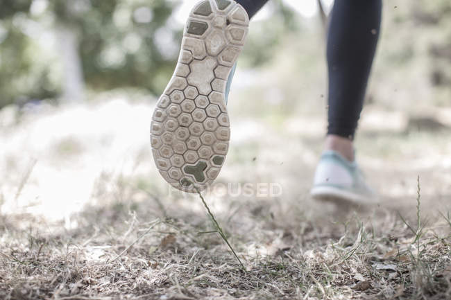 Close-up of feet of woman running in forest — Stock Photo
