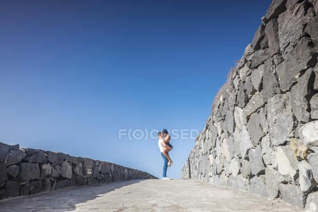 España, Tenerife, pareja joven enamorada delante del cielo azul - foto de stock