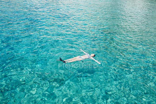 Grèce, Milos, femme flottant sur l'eau turquoise — Photo de stock