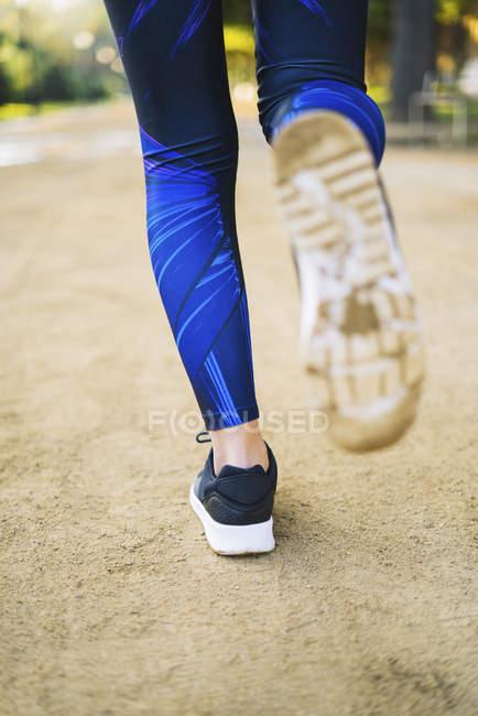 Close-up image of legs of running female athlete — Stock Photo