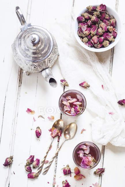 Чайник и два стакана чая с розами и сушеными цветами роз — стоковое фото