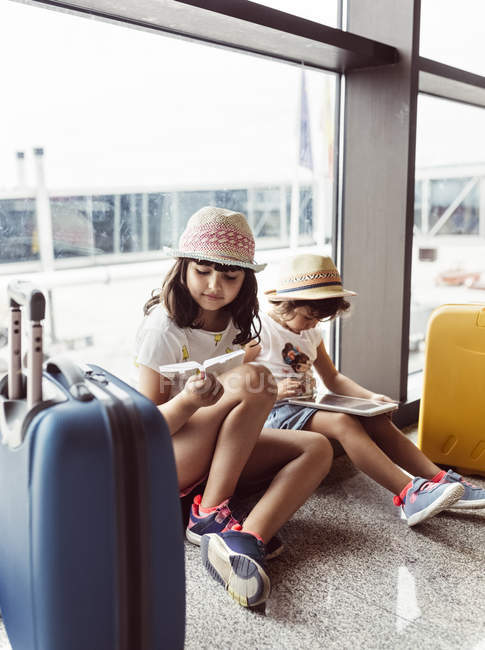 Two little girls waiting at airport, playing with digital tablet — Stock Photo