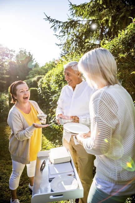 Щасливі похилого віку друзів, що стояв зі стравами в саду — стокове фото
