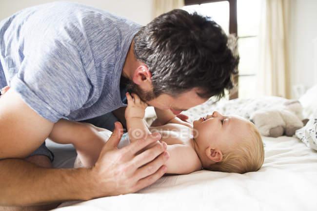 Щасливий батько прокладки з дитиною на ліжку — стокове фото