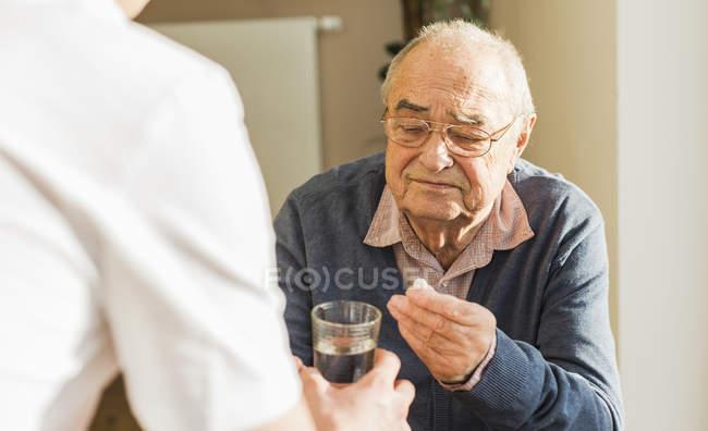 Senior homme se comprime et verre d'eau — Photo de stock