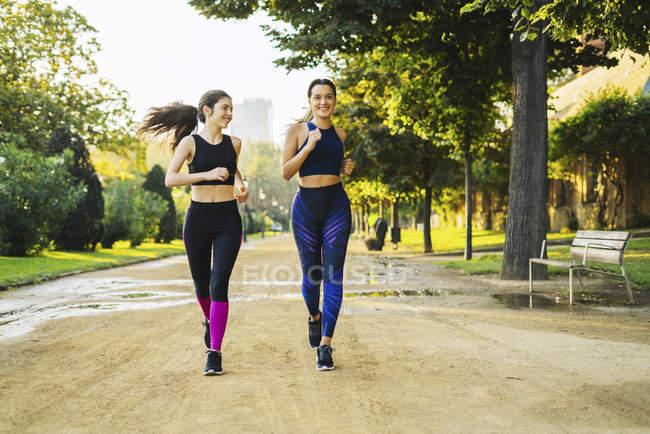 Две молодые женщины бегают в парке — стоковое фото