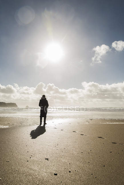 Woman standing on the beach at backlit, France, Bretagne, Finistere, Crozon peninsula — Stock Photo